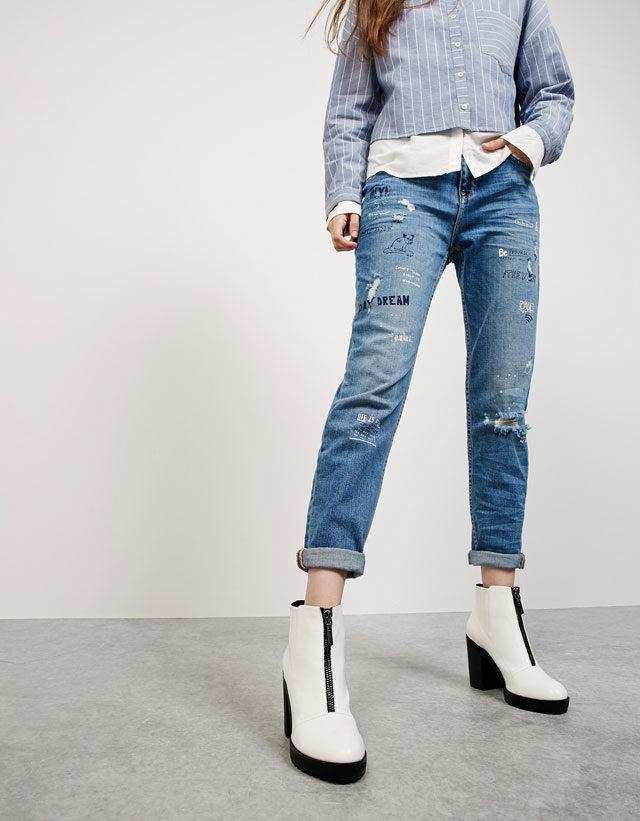 Bershka: jeans Boyfriend con scritte e strappi.