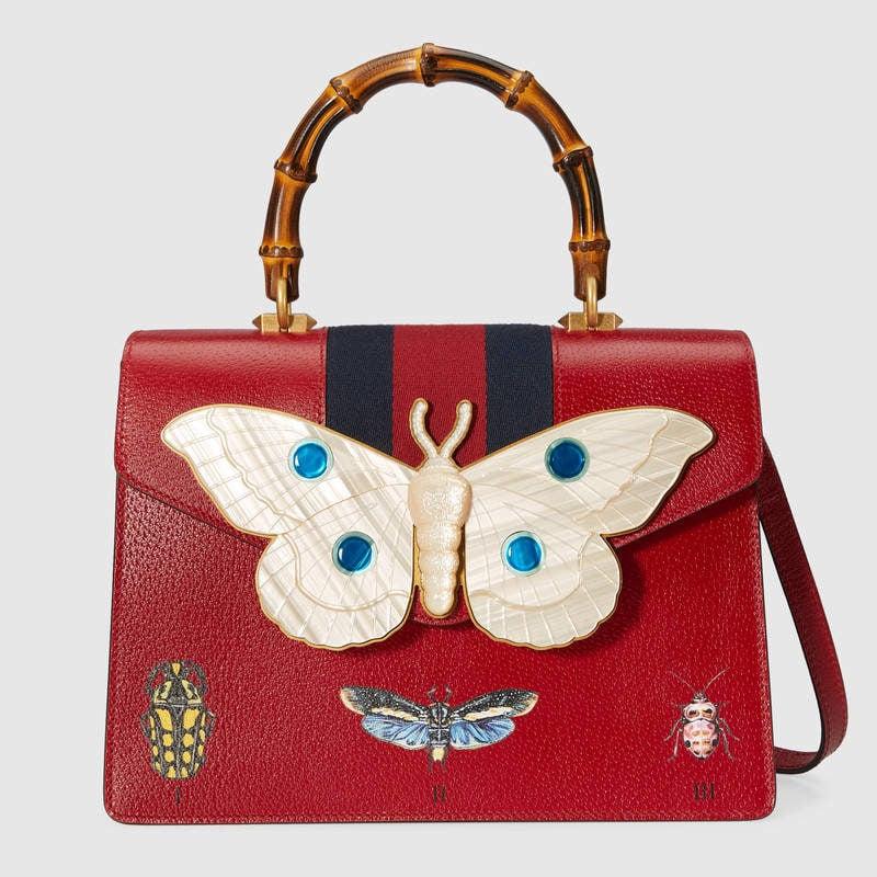 Borsa a mano in pelle misura media rossa con farfalla applicata.