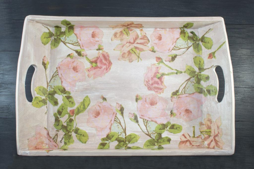 Un vassoio di legno realizzato con la tecnica del decoupage con un motivo floreale.